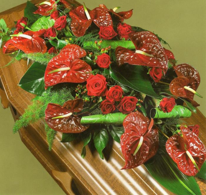 Kistbedekking van rode rozen en anthuriums € 275,00