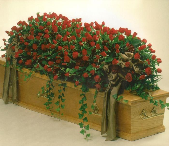 Kistbedekking van rode rozen en hedera € 410,00
