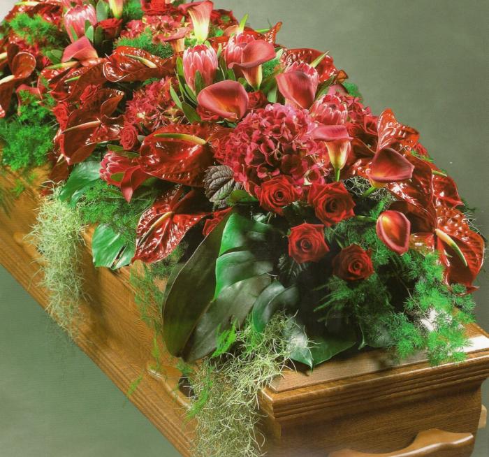 Kistbedekking van rode rozen, anthuriums, protea's e.d. € 520,00